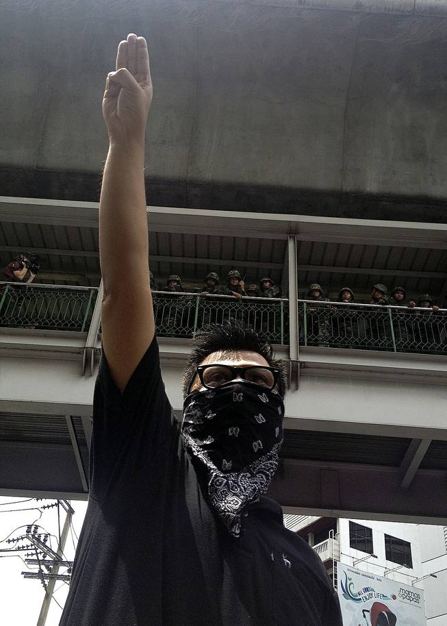 "In this June 1, 2014, photo, an anti-coup protester gives a three-finger salute as soldiers keep eyes on him from an elevated walkway near a rally site in central Bangkok, Thailand. Thailand's military rulers say they are monitoring the new form of silent resistance to the coup — borrowed from ""The Hunger Games"" — and will arrest those in large groups who ignore warnings to lower their arms."