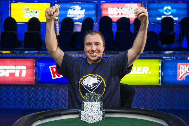 Jonathan Dimmig holds his World Series of Poker bracelet and winning hand at the Rio after emerging victorious in the 2014 Millionaire Maker tournament for $1.3 million.