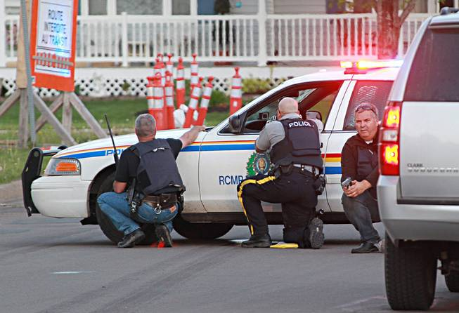 Police officers take cover behind their vehicles in Moncton, New Brunswick, on Wednesday, June 4, 2014. Three police officers were shot dead and two others injured Wednesday in the east coast Canadian province of New Brunswick.
