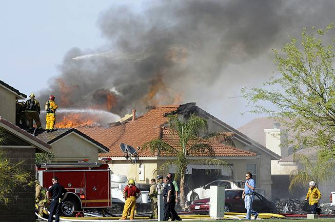 This photo shows the site of a military jet that crashed on a residential street in Imperial, Calif., setting two homes on fire Wednesday, June 4, 2014. Lance Cpl. Christopher Johns, a U.S. Marines spokesman, says the jet was a Harrier from Marine Corps Air Station in Yuma, Ariz.