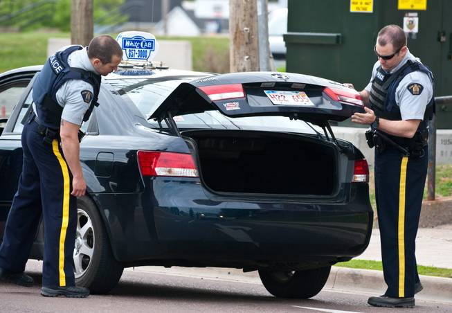 Royal Canadian Mounted Police check the trunk of a taxi at a roadblock in Moncton, New Brunswick on Thursday, June 5, 2014. A RCMP manhunt for a gunman suspected of killing three Mounties and wounding two others passed the 12-hour mark Thursday in Moncton as a large section of the New Brunswick city was under a virtual siege.