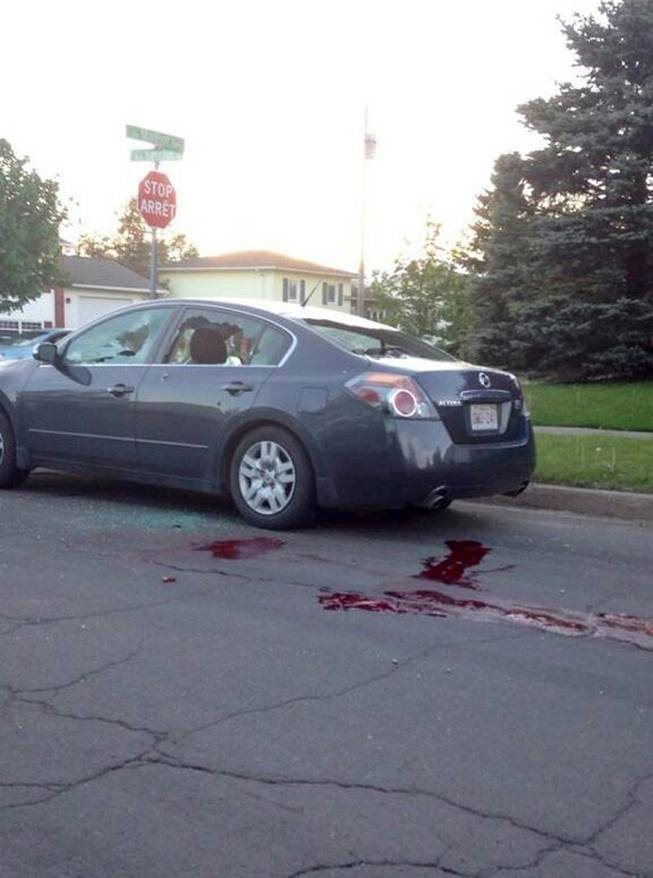 A car sits on a road with it's windows shot out and blood on the ground in Moncton, New Brunswick on Wednesday, June 4, 2014. The Royal Canadian Mounted Police says three of its officers were killed in Moncton, New Brunswick by a man armed with guns and two other officers were injured as the Mounties conducted a manhunt across the city's north end on Wednesday night for the shooter.
