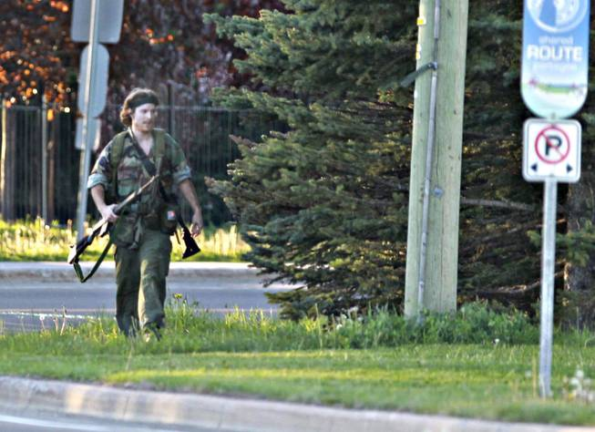 A heavily armed man that police have identified as Justin Bourque walks on Hildegard Drive in Moncton, New Brunswick, on Wednesday, June 4, 2014, after several shots were fired in the area. The man, suspected of killing three Royal Canadian Mounted Police officers, was spotted three times Thursday but has so far eluded a massive manhunt, police said.