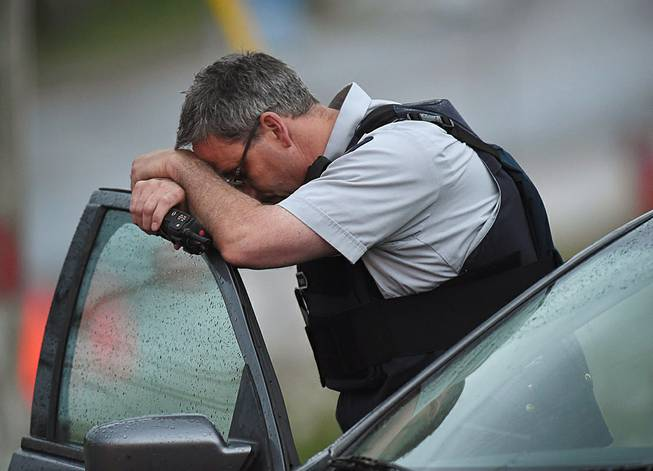 A Royal Canadian Mounted Police officer rests his head at a roadblock in Moncton, New Brunswick, on Thursday, June 5, 2014. RCMP officers combed the streets and woods of this normally tranquil city Thursday in search of a man suspected of killing three officers in the deadliest attack on their ranks in nearly a decade.