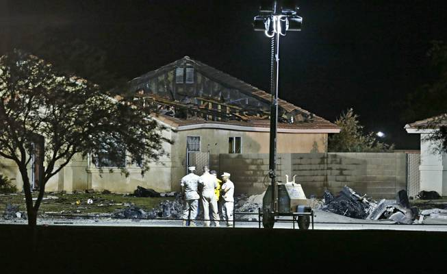 Officials stand outside a home in which the roof is burnt off after a Marine Harrier jet crashed into the neighborhood Wednesday, June 4, 2014, in Imperial, Calif. The pilot and everyone on the ground escaped unscathed, officials said. Debris from the jet is on the ground to the right.