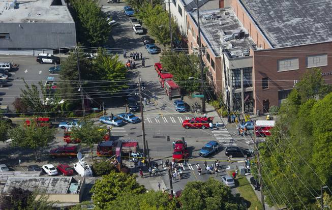 In an aerial view, authorities and other emergency responders gather near Otto Miller Hall, upper left, at Seattle Pacific University on Thursday, June 5, 2014, in Seattle. Police say a university student on Thursday disarmed a lone gunman who entered a building and shot four people. A hospital spokeswoman says one man has died and three other people are injured, one critically. (AP Photo/The Seattle Times, Ellen M. Banner) SEATTLE OUT   USA TODAY OUT  MAGS OUT; NO SALES; TV OUT; MANDATORY CREDIT TO BOTH THE SEATTLE TIMES AND THE PHOTOGRAPHER