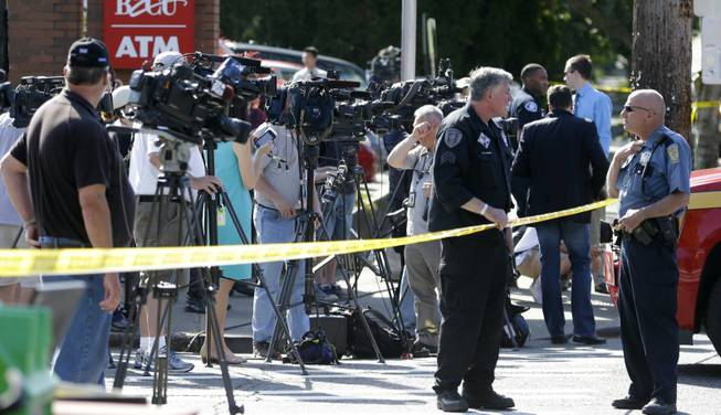 Television videographers and other media wait for a briefing at the scene of a shooting Thursday, June 5, 2014, at Seattle Pacific University in Seattle. (AP Photo/Ted S. Warren)
