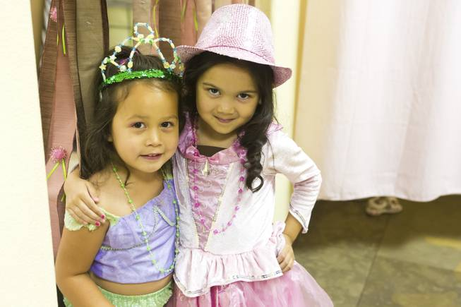 Reece, 3, and Mia, 5, pose for a photo after trying on some party costumes at Rock the Tea, Tuesday June 3, 2014. Rock the Tea is a themed party-hosting service for young girls.