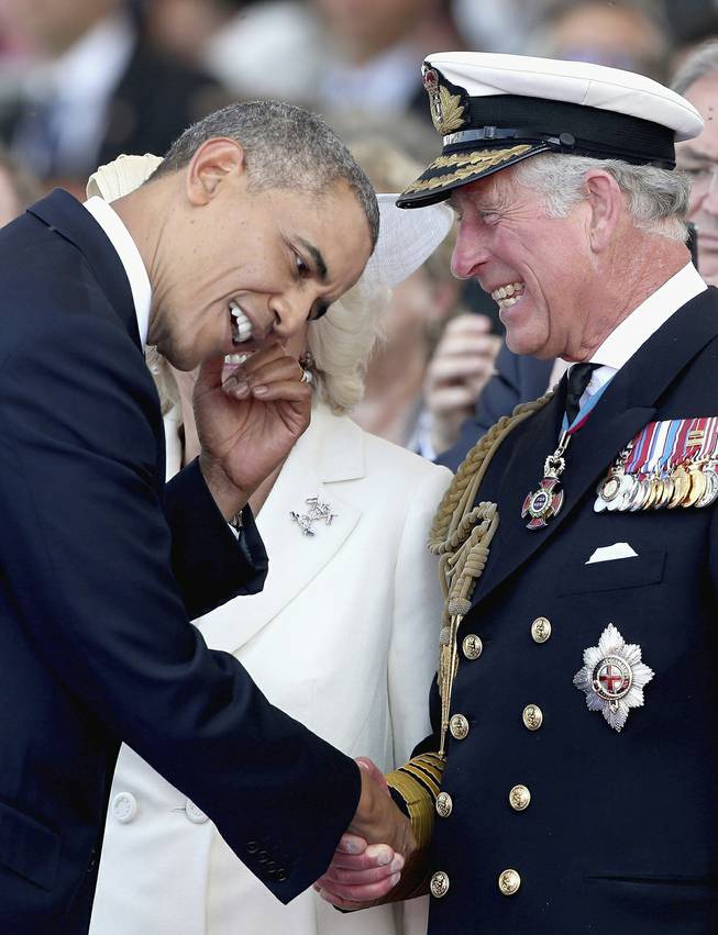 Britain's Prince Charles, right,  laughs as he meets U.S. President Barak Obama, during an International Ceremony with Heads of State at Sword Beach Ouistreham, France  to mark the 70th Anniversary of the D-Day landings Friday June 6, 2014.