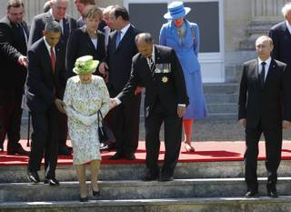 Russian President Vladimir Putin stands at right as U.S. President Barack Obama, left, and New Zealand's Governor-General Jerry Mateparae guide Britain's Queen Elizabeth II to her position for a group photo, with French President Francois Hollande, in the background, talking with German Chancellor Angela Merkel, as they take part in commemorations for  the 70th anniversary of the D-Day landings,  in Benouville in Normandy, France, Friday, June 6, 2014.