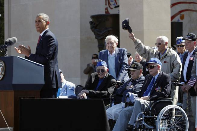 U.S. President Barack Obama, left, acknowledges veterans as he speaks at the Normandy American Cemetery, at Omaha Beach as he participates in the 70th anniversary of D-Day in Colleville sur Mer in Normandy, France, Friday, June 6, 2014.