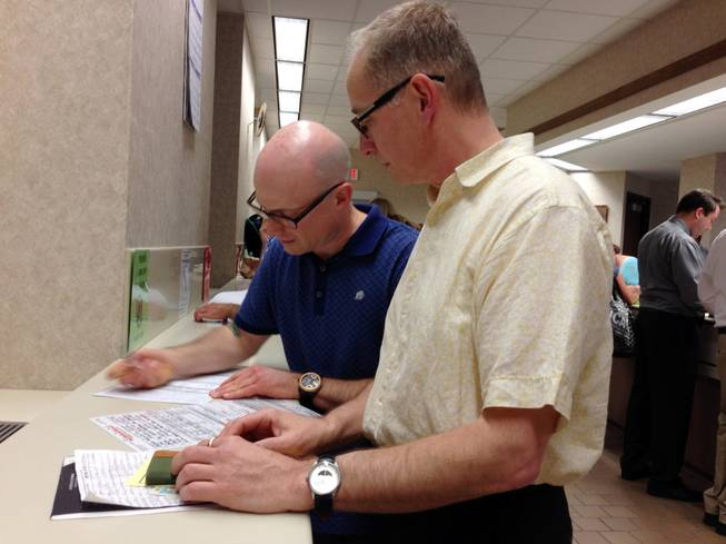 Mark Williams, left, and Chrisopher Martell, right, fill out an application for a marriage license at the Milwaukee County Clerk's office Friday, June 6, 2014, in Milwaukee. Same-sex couples began getting married in Wisconsin on Friday shortly after a federal judge struck down the state's gay marriage ban and despite confusion over the effect of the ruling.