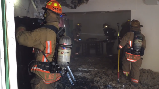 In an image captured from a Las Vegas Fire & Rescue video, firefighters work in the aftermath of a fire that started about 5 a.m. Friday, June 6, 2014, in a house in the 1900 block of Wengert Avenue. Officials said six people were taken to University Medical Center with smoke inhalation.