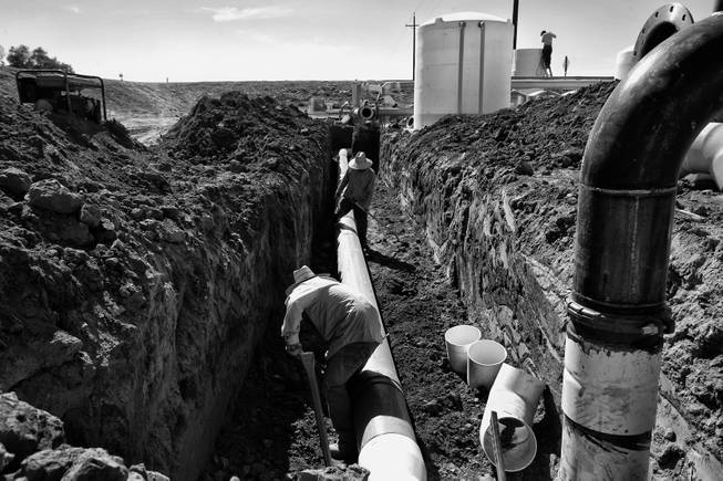 Workers install pipe to a new well in Huron, California. During the season the areas farms need the most labor the work force doubles, but a drought has cut production and workers find trouble landing positions in the fields.