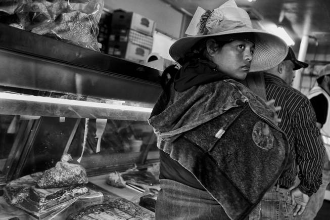 A woman just returned from working in the fields waits to make a purachase at a butcher in Huron, California. During the season the areas farms need the most labor the work force doubles, but a drought has cut production and workers find trouble landing positions in the fields.