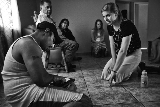 Francisco Galvez, sits on the floor of his home as a Mormon missionary makes her pitch to him and his family in Huron, California. During the season the areas farms need the most labor the work force doubles, but a drought has cut production and workers find trouble landing positions in the fields.
