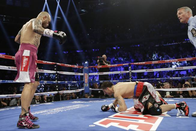 Miguel Cotto, of Puerto Rico, knocks down Sergio Martinez, of Argentina, during the first round of a WBC World Middleweight Title boxing match Saturday, June 7, 2014, in New York. Cotto won the fight. (AP Photo/Frank Franklin II)