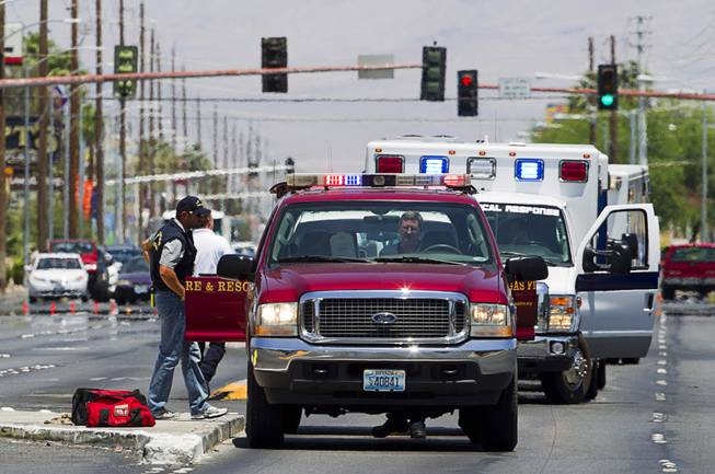 Ambulances and rescue units stage on Nellis Boulevard Sunday, June 8, 2014. Two suspects shot two Metro Police officers in a nearby pizza shop then fled to the Wal-Mart where they shot and killed another person, police said. Both officers died of their injuries.