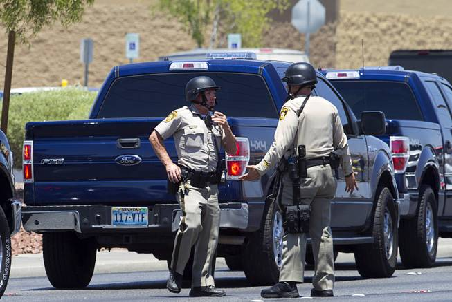 Metro Police officers confer outside a Wal-Mart on Nellis Boulevard Sunday, June 8, 2014. Two suspects shot two Metro Police officers in a nearby pizza shop then fled to the Wal-Mart where they shot and killed another person, police said. Both officers died of their injuries.
