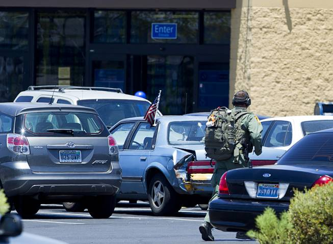 A Metro Police officer runs through the Wal-Mart parking lot on Nellis Boulevard Sunday, June 8, 2014. Two suspects shot two Metro Police officers in a nearby pizza shop then fled to the Wal-Mart where they shot and killed another person, police said. Both officers died of their injuries.