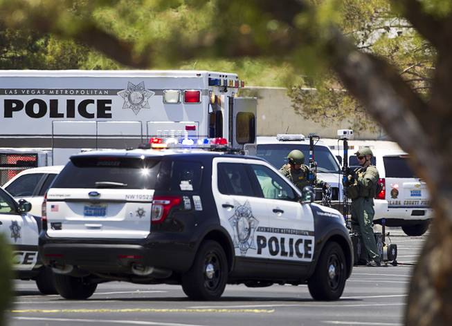 Metro Police officers set up equipment in the parking lot of a Wal-Mart on Nellis Boulevard Sunday, June 8, 2014. Two suspects shot two Metro Police officers in a nearby pizza shop then fled to the Wal-Mart where they shot and killed another person, police said. Both officers died of their injuries.