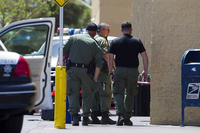 Metro Police officers are shown outside a Wal-Mart on Nellis Boulevard Sunday, June 8, 2014. Two suspects shot two Metro Police officers in a nearby pizza shop then fled to the Wal-Mart where they shot and killed another person, police said. Both officers died of their injuries.