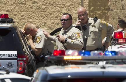 Metro Police are seen outside a Wal-Mart on Nellis Boulevard between Charleston Boulevard and Stewart Avenue where two people suspected of shooting Metro officers at Cici's Pizza, 309 N. Nellis Blvd., ran Sunday morning.