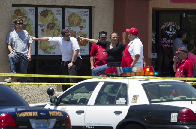 Bystanders watch police activity from a Roberto's Taco Shop behind a Wal-Mart on Nellis Boulevard on Sunday, June 8, 2014. Two suspects allegedly shot two Metro Police officers in a nearby pizza shop, then fled to the Wal-Mart, where they fired shots before killing themselves.