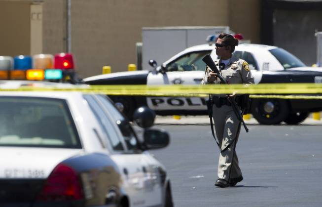 A Metro Police officer is shown behind a Wal-Mart on Nellis Boulevard on Sunday, June 8, 2014. Two suspects allegedly shot two Metro Police officers in a nearby pizza shop, then fled to the Wal-Mart, where they fired shots before killing themselves.