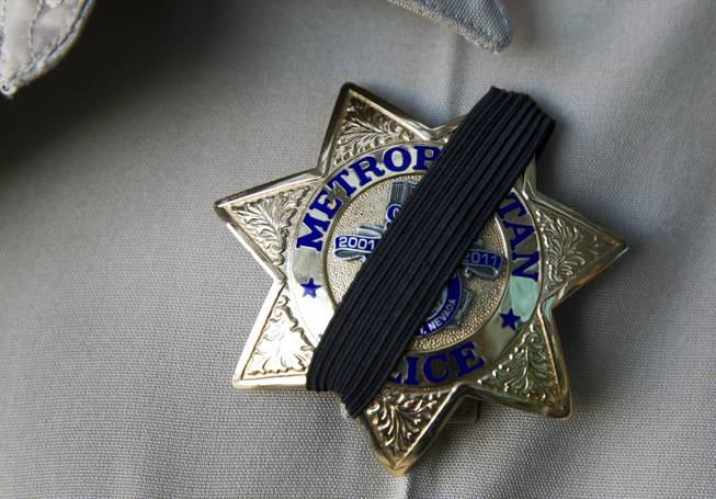 A Metro Police officer wears a ribbon over his badge at Metro headquarters following the death of two officers and a citizen Sunday, June 8, 2014. Two suspects, also dead, shot two Metro Police officers at CiCi's Pizza on Nellis Boulevard, then fled to a nearby Wal-Mart, where they shot and killed another person before killing themselves, police said.