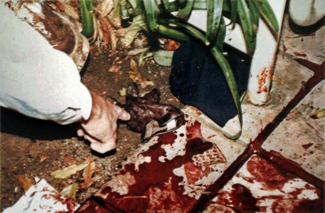 This June 13, 1994, file evidence photo provided by the Los Angeles Police Department shows LAPD's Mark Fuhrman pointing to a pieces of evidence near the body of Nicole Brown Simpson on the bloodstained walkway of her condominium. The photo was introduced as evidence and released for publication, in the 1996 O.J. Simpson wrongful-death civil trial. The O.J. Simpson trial has become a textbook example of what not to do at a crime scene for police and forensic workers.