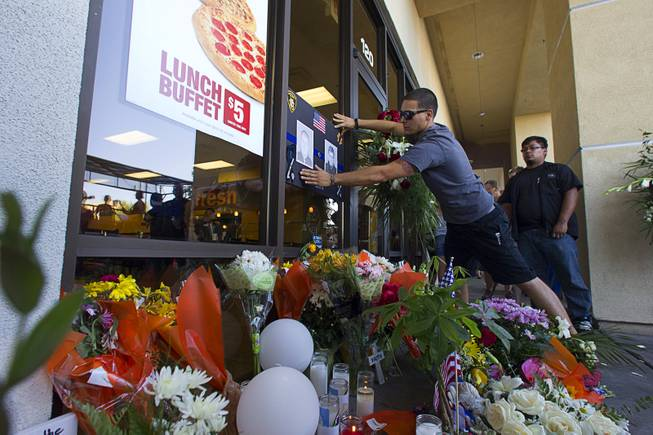 Anthony Gariano puts up a sign at a memorial in front of CiCi's Pizza shop, where two Metro Police officers were killed, during a community vigil Monday, June 9, 2014. Police officers Alyn Beck, 41, and Igor Soldo, 31, were ambushed and killed in the restaurant while they were eating lunch on June 8.