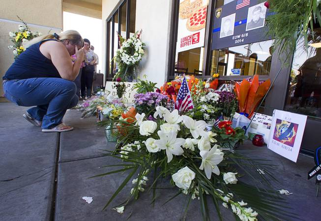 Brenda Williams pays her respects at a memorial in front of CiCi's Pizza, where two Metro Police officers were killed, during a community vigil Monday, June 9, 2014. Police officers Alyn Beck, 41, and Igor Soldo, 31, were ambushed and killed in the restaurant while they were eating lunch on June 8.