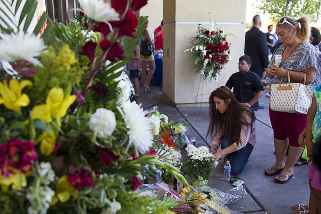 Natalie Vazquez, left, and her aunt Gina Avila light candles at a memorial in front of CiCi's Pizza, where two Metro Police officers were killed, during a community vigil Monday,, Nevada June 9, 2014. Police officers Alyn Beck, 41, and Igor Soldo, 31, were ambushed and killed in the restaurant while they were eating lunch on June 8.