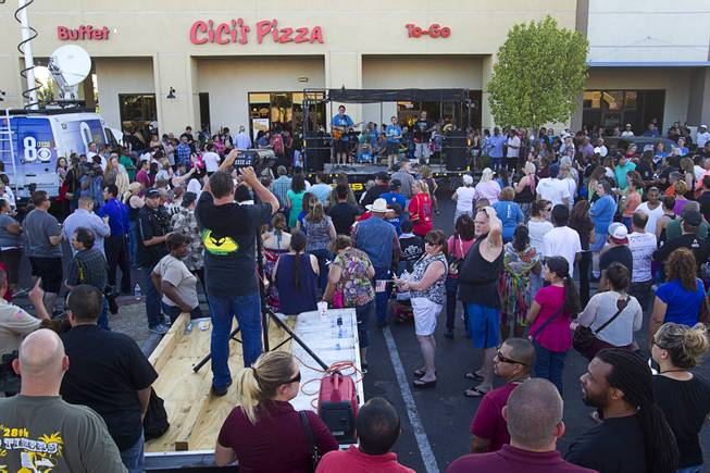People attend a community vigil for slain Metro Police officers in front of CiCi's Pizza Monday,, Nevada June 9, 2014. Officers Alyn Beck, 41, and Igor Soldo, 31, were ambushed and killed in the restaurant while they were eating lunch on June 8.