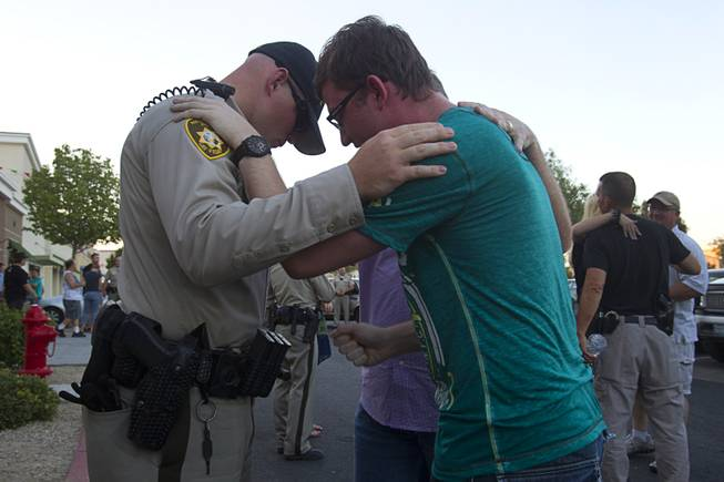 Metro Police officer Harrison Porter, left, prays with Ryan Rasmussen during a community vigil for slain Metro Police officers at CiCi's Pizza Monday,, Nevada June 9, 2014. Officers Alyn Beck, 41, and Igor Soldo, 31, were ambushed and killed in the restaurant while they were eating lunch on June 8.