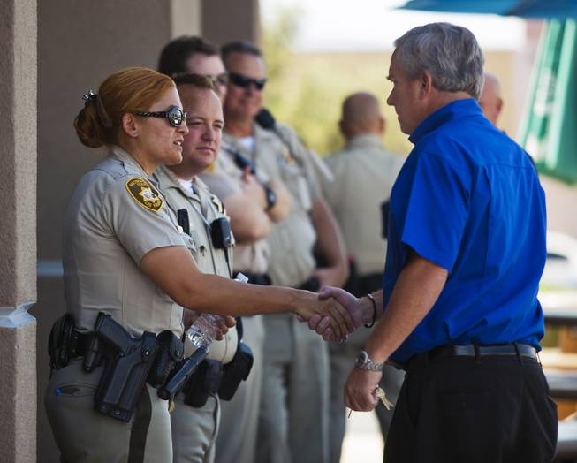 Metro Police officers are consoled by Mike Haskins as they gather across from CiCi's Pizza restaurant in Las Vegas to honor their fallen brothers on Monday, June 9, 2014.