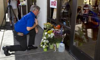 Mike Haskins says a prayer after leaving flowers at a CiCi's Pizza restaurant in honor of two Metro Police officers killed there on Sunday, June 8, 2014. A small memorial was building there and officers were gathered nearby as well in support of their fallen comrades on Monday, June 9, 2014.
