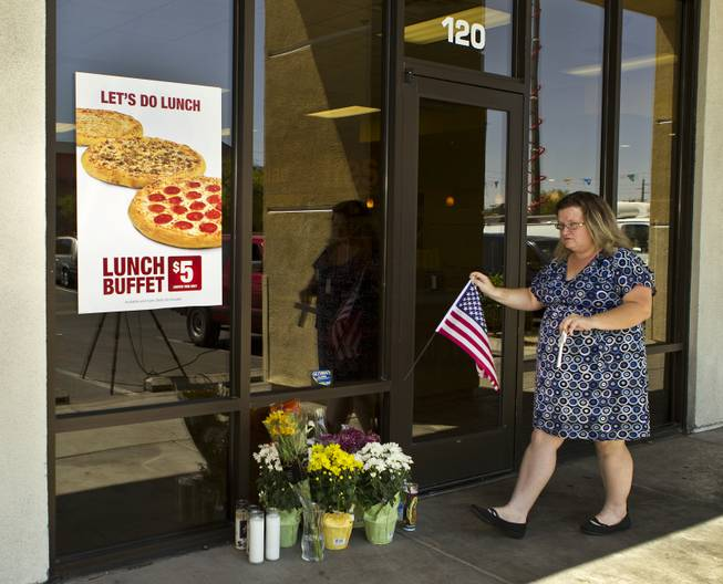 McKenzie Weiss arrives flowers and a cross at a CiCi's Pizza restaurant in honor of two Metro Police officers killed there on Sunday, June 8, 2014. A small memorial was building there and officers were gathered nearby as well in support of their fallen comrades on Monday, June 9, 2014.