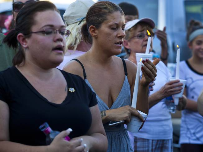 Community members sing with lit candles to honor slain Metro Police officers Alyn Beck and Igor Soldo during a candlelight vigil outside of CiCi's Pizza restaurant on Monday, June 9, 2014.