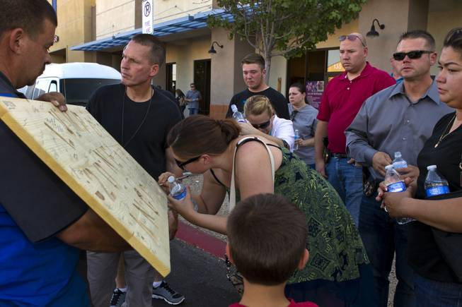 Metro Police officers, family and friends take turns to sign a wooden plaque created by Jason Proctor to honor slain officers Alyn Beck and Igor Soldo on Monday, June 9, 2014.  Many were on hand during a candlelight vigil outside of CiCi's Pizza restaurant to show their support.