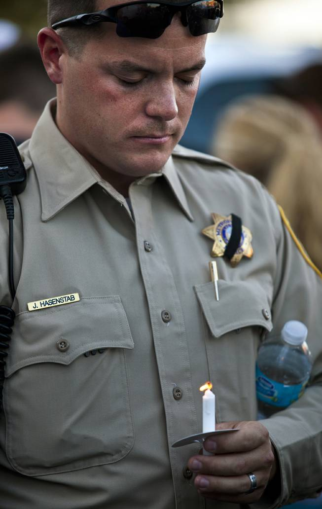 Metro Police officer J. Hasenstab bows his head with lit candle during a candlelight vigil to show support for slain officers Alyn Beck and Igor Soldo outside of CiCi's Pizza restaurant on Monday, June 9, 2014.