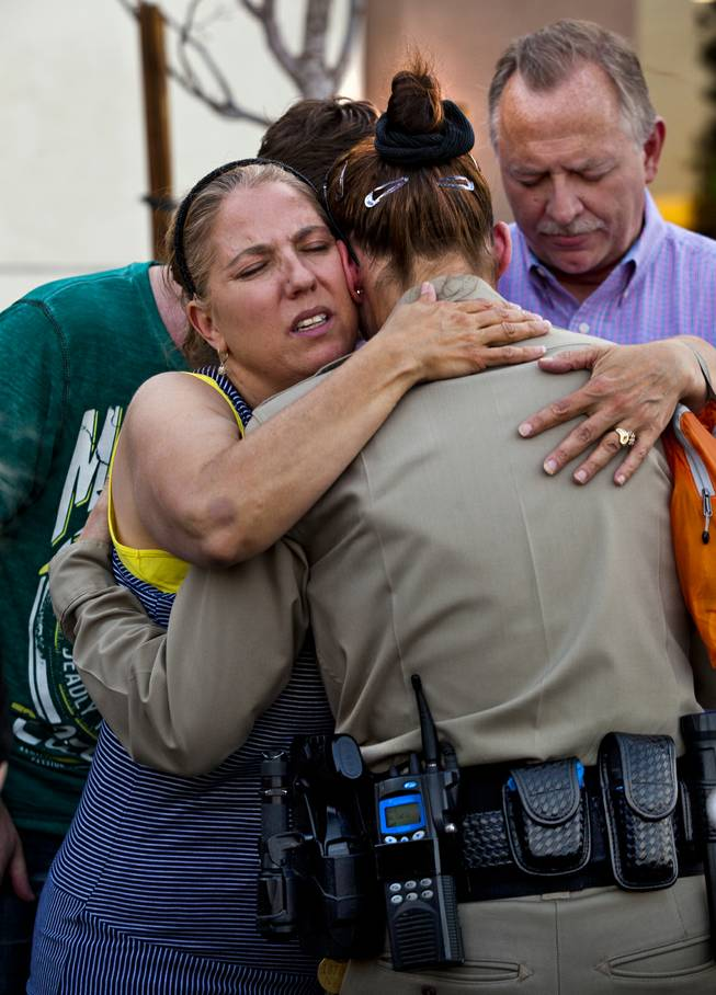 Cheri Rasmussen with the International Church of Las Vegas hugs Metro Police officer T. Bonner following a candlelight vigil outside of CiCi's Pizza restaurant to honor slain officers Alyn Beck and Igor Soldo on Monday, June 9, 2014.  They are joined by Ryan and Mark Rasmussen.