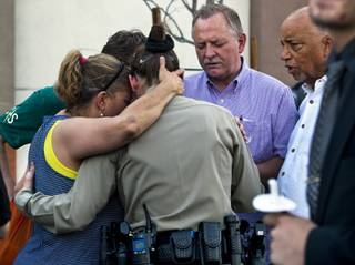 Cheri Rasmussen with the International Church of Las Vegas prays with Metro Police officer T. Bonner following a candlelight vigil outside of CiCi's Pizza restaurant to honor slain officers Alyn Beck and Igor Soldo on Monday, June 9, 2014.  They are joined by Ryan and Mark Rasmussen and other supporters.