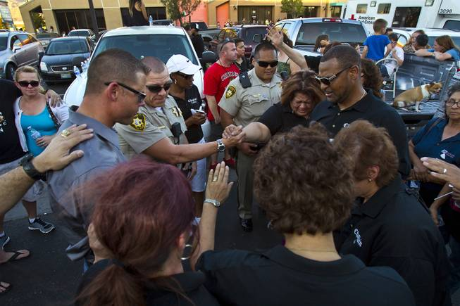 Metro Police officers, family and supporters pray to honor slain officers Alyn Beck and Igor Soldo following a candlelight vigil outside of CiCi's Pizza restaurant on Monday, June 9, 2014.