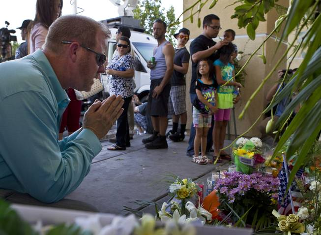 A man prays about a memorial to slain Metro Police officers Alyn Beck and Igor Soldo as community members  gather for a candlelight vigil in their honor outside of CiCi's Pizza restaurant on Monday, June 9, 2014.