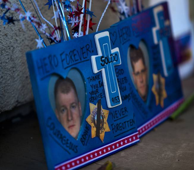 A memorial to slain Metro Police officers Alyn Beck and Igor Soldo grows as community members  gather for a candlelight vigil in their honor outside of CiCi's Pizza restaurant on Monday, June 9, 2014.