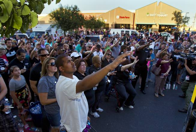 Community members gather to honor slain Metro Police officers Alyn Beck and Igor Soldo with music, prayer and a candlelight vigil outside of CiCi's Pizza restaurant on Monday, June 9, 2014.