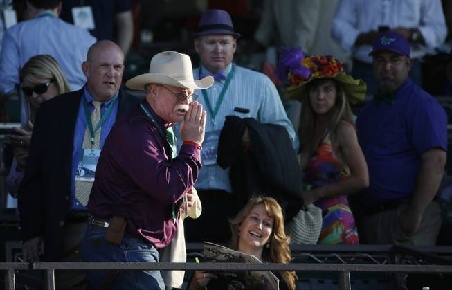 California Chrome co-owner Steve Coburn calls from the grandstand at Belmont Park after his horse finished fourth in the Belmont Stakes horse race, Saturday, June 7, 2014, in Elmont, N.Y.