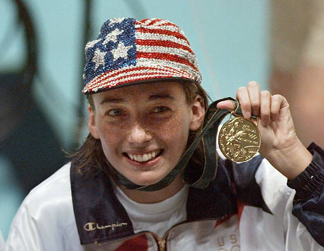 In this July 26, 1996 file photo, Olympic gold medalist Amy Van Dyken holds her medal after winning the women's 50 meter freestyle at the 1996 Summer Olympic Games in Atlanta. Van Dyken has a severed spine after an accident on her all-terrain vehicle in Arizona.